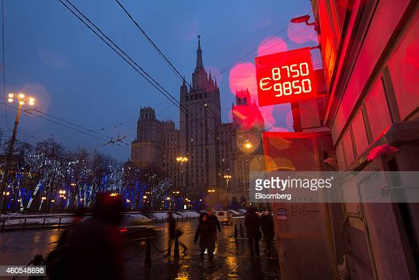 Pedestrians pass a neon sign displaying the latest Russian ruble euro dollar exchange rate outside a currency exchange bureau in Moscow Russia on...