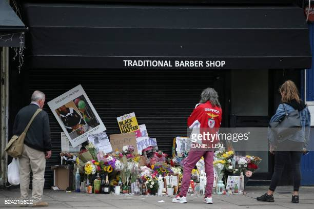 Pedestrians pass a pile of floral tributes and candles for Rashan Charles whose death after being followed by police into a convenience store and...