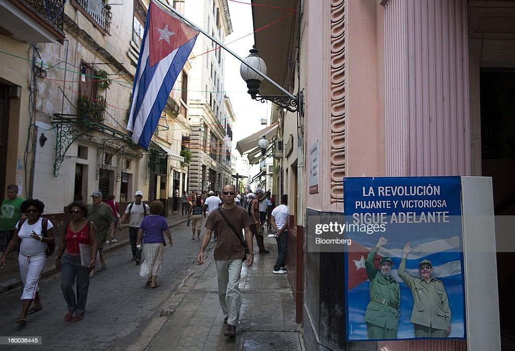 Pedestrians pass a poster of brothers Fidel and Raul Castro and a Cuban national flag in a street in central Havana, Cuba, on Thursday, Jan. 17, 2013. In a country where the average monthly salary is $19, according to Cuba's statistics agency, even buying an airplane ticket will be beyond the reach of most of the island's 11 million residents as President Raul Castro begins easing travel rules on the communist island. Photographer: Andrey Rudakov/Bloomberg via Getty Images