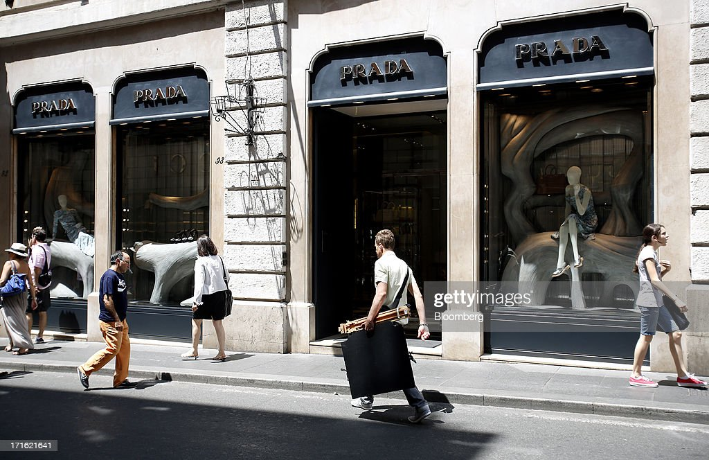 Pedestrians pass a Prada SpA store as they walk along Via Condotti in Rome, Italy, on Wednesday, June 26, 2013. Italian household confidence rose this month as consumers grew optimistic about the country's outlook as Prime Minister Enrico Letta's government plans to cut taxes and boost youth employment. Photographer: Alessia Pierdomenico/Bloomberg via Getty Images