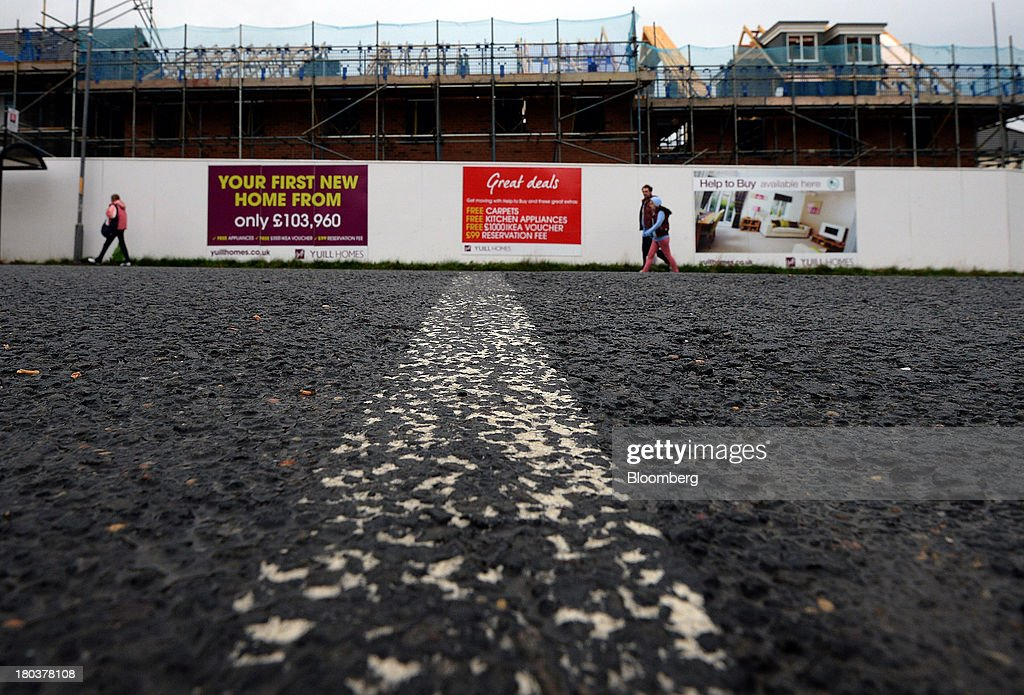 Pedestrians pass a residential housing development at a Yuill Homes construction site, operated by Cecil M Yuill Ltd., in Newcastle-upon-Tyne, U.K., on Wednesday, Sept. 11, 2013. U.K. house prices rose for a seventh month in August and will probably continue to increase through the rest of the year, according to a report by Halifax. Photographer: Nigel Roddis/Bloomberg via Getty Images