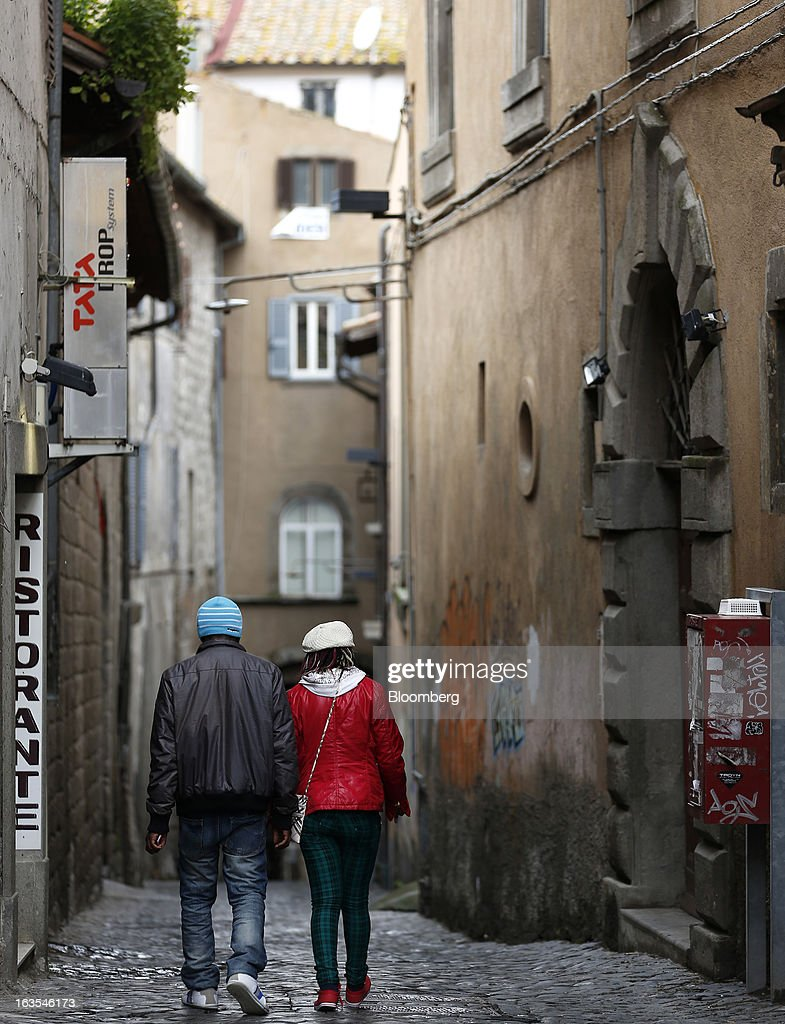 Pedestrians pass a restaurant as they walk down a cobbled side street in Viterbo, Italy, on Monday, March 11, 2013. Intesa Sanpaolo SpA and UniCredit SpA are among Italian banks due to report losses for the fourth quarter this week, as the economic contraction meant more clients failed to repay their debts. Photographer: Alessia Pierdomenico/Bloomberg via Getty Images