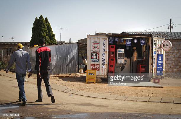Pedestrians pass a roadside store offering an MPesa mobile phone money transfer service operated by Standard Bank Group Ltd in Tembisa near...