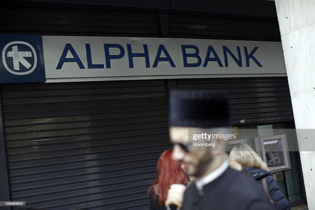 Pedestrians pass a shuttered branch of Alpha Bank AE in Athens, Greece, on Tuesday, Jan. 22, 2013. Euro-area finance ministers blessed the next disbursement of emergency aid for Greece, highlighting the goodwill that led to the unblocking of loans last month for Prime Minister Antonis Samaras's government. Photographer: Kostas Tsironis/Bloomberg via Getty Images