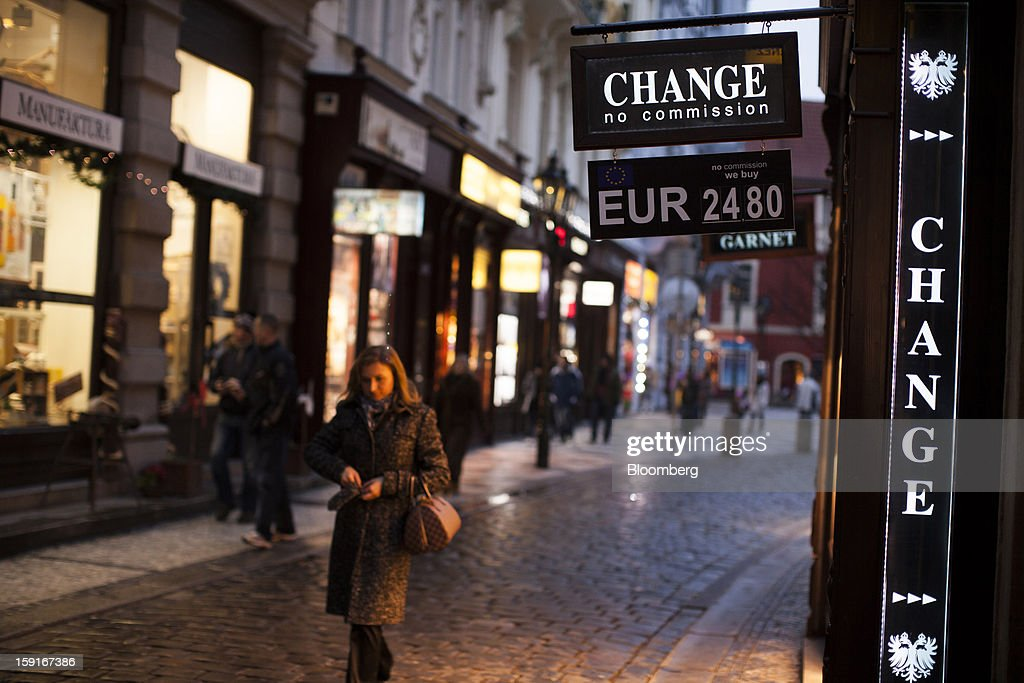 Pedestrians pass a sign advertising euro currency rates outside a money exchange in Prague, Czech Republic, on Tuesday, Jan. 8, 2013. The Czech economy is showing weak domestic demand as households and businesses cut spending due to government austerity programs and the euro area's debt crisis. Photographer: Bartek Sadowski/Bloomberg via Getty Images