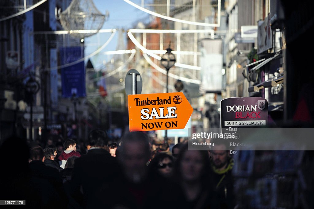Pedestrians pass a sign directing shoppers towards a sale of Timberland Co. goods on Grafton Street in Dublin, Ireland, on Thursday, Dec. 27, 2012. Ireland will take over the EU presidency in January as the euro-area wrestles with putting the European Central Bank in charge of lenders within the currency union and other participating nations. Photographer: Aidan Crawley/Bloomberg via Getty Images