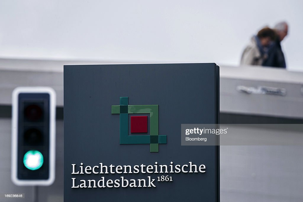 Pedestrians pass a sign near the offices of Liechtensteinische Landesbank AG (LLB) in Vaduz, Liechtenstein, on Tuesday, May 21, 2013. Liechtenstein, an alpine principality once fabled for its banking secrecy laws, remains a place favored by billionaires to stash the holding companies and investment entities that control their assets. Photographer: Valentin Flauraud/Bloomberg via Getty Images