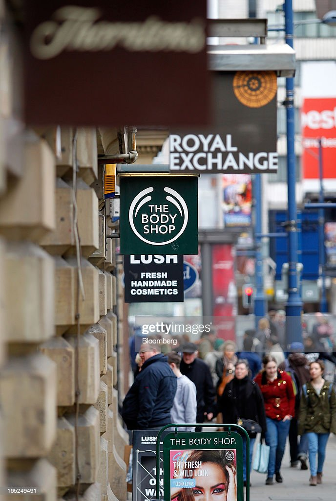 Pedestrians pass a sign outside a Body Shop International Plc store in Manchester, U.K., on Monday, April 1, 2013. U.K. retail sales unexpectedly stagnated in March in a sign that consumer spending remains under pressure from higher energy bills and weak wage growth. Photographer: Paul Thomas/Bloomberg via Getty Images