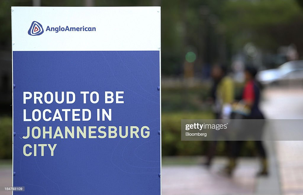 Pedestrians pass a sign reading 'Proud to be located in Johannesburg City' outside the offices of Anglo American Plc in the Marshalltown district of Johannesburg, South Africa, on Friday, Oct. 26, 2012. Anglo American Plc Chief Executive Officer Cynthia Carroll , the first woman, external hire and non-South African to hold the job, will quit after Anglo lost $14 billion in value in the more than five years she was in charge. Photographer: Chris Ratcliffe/Bloomberg via Getty Images