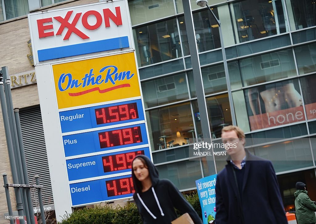 Pedestrians pass a sign showing gas prices at an Exxon station on February 19, 2013 in the Foggy Bottom neighbourhood of Washingon, DC. US gas prices at the pumps have risen for over 30 days consecutively to a four-month high. According to the AAA, the national average for a gallon of regular gas is $3.748. AFP PHOTO/Mandel NGAN