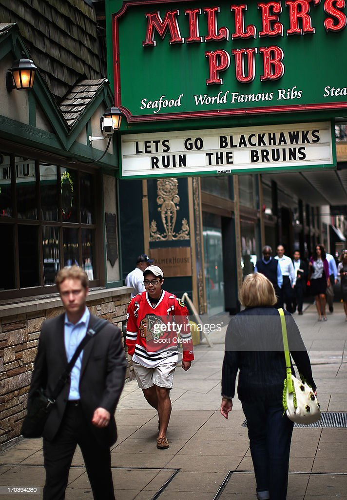 Pedestrians pass a sign showing support for the Chicago Blackhawks in the Loop on June 12, 2013 in Chicago, Illinois. The Chicago Blackhawks will match up against the Boston Bruins tonight at the United Center in the first game on the NHL Stanley Cup playoffs.