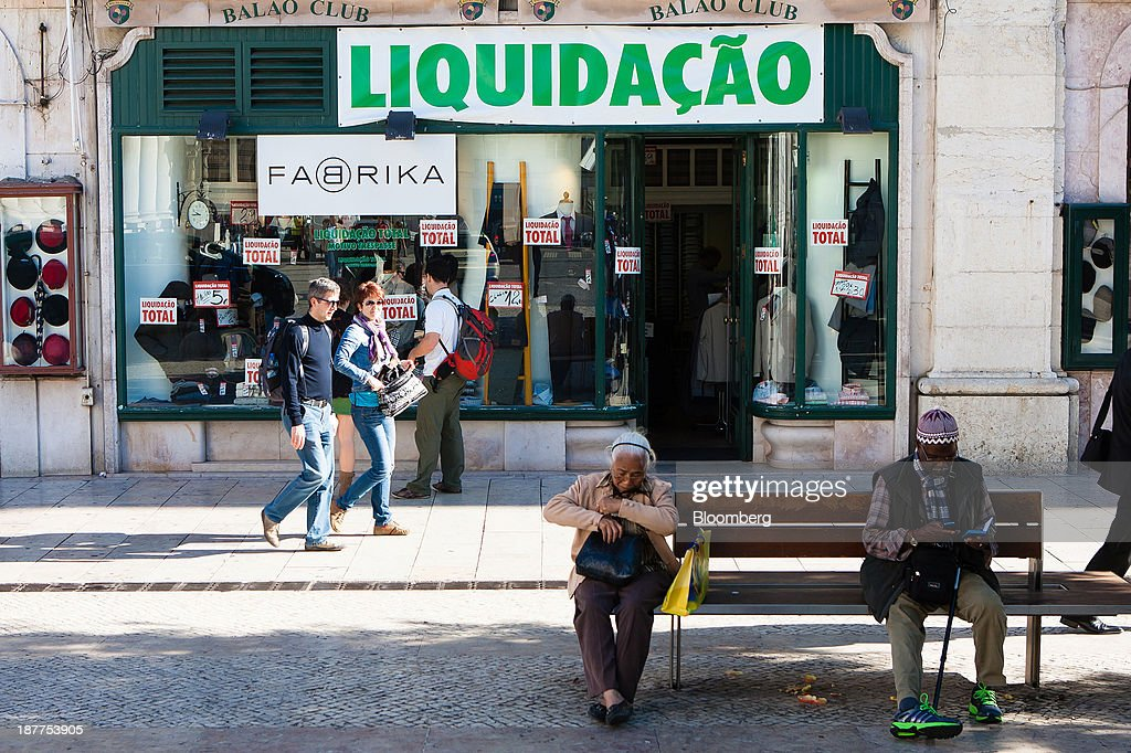 Pedestrians pass a store advertising a stock clearance sale above its window display in Lisbon, Portugal, on Tuesday, Nov. 12, 2013. Portugal's jobless rate dropped for a second quarter, falling to 15.6 percent in the three months through September as the country's economy shows signs of recovery. Mario Proenca/Bloomberg via Getty Images