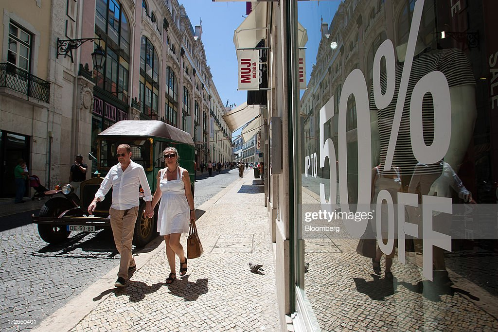 Pedestrians pass a store advertising fifty percent discounts in Lisbon, Portugal, on Wednesday, July 3, 2013. Portuguese borrowing costs topped 8 percent for the first time this year after two ministers quit, signaling the government will struggle to implement further budget cuts as its bailout program enters its final 12 months. Photographer: Mario Proenca/Bloomberg via Getty Images