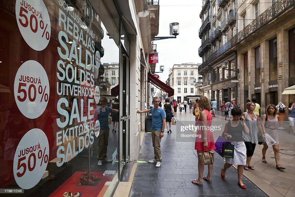 Pedestrians pass a store offering discounted goods for sale on Rue Sainte-Catherine, the main shopping street in Bordeaux, France, on Wednesday, July 17, 2013. Austerity measures and rising unemployment are restraining consumer spending in Europe, while retailers including Groupe Auchan SA and Casino Guichard-Perrachon SA are competing more aggressively on price. Photographer: Balint Porneczi/Bloomberg via Getty Images