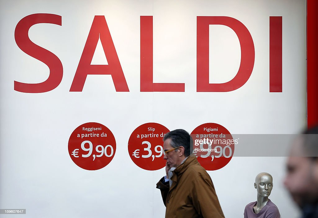 Pedestrians pass a store window advertising a sale in Milan, Italy, on Thursday, Jan. 17, 2013. The euro-area economy won't return to growth until the next quarter as a recovery in Italy is delayed and France continues to shrink, according to a survey of economists. Photographer: Alessia Pierdomenico/Bloomberg via Getty Images