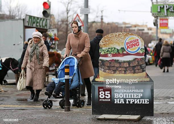 Pedestrians pass a street advertisement outside a Burger King fast food restaurant in Moscow Russia on Friday April 5 2013 McDonald's which virtually...