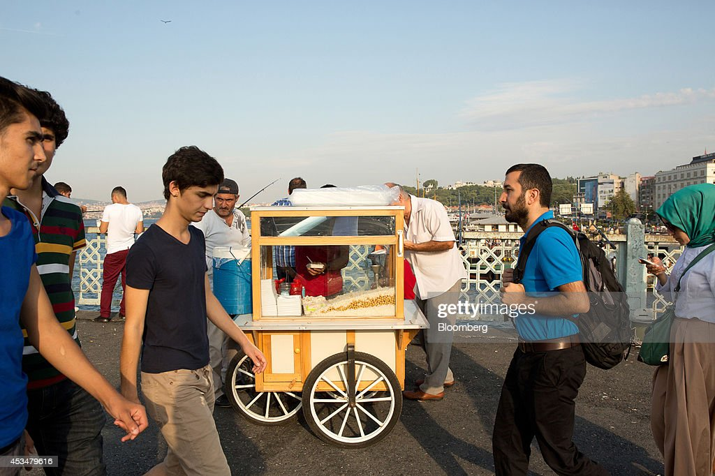 Pedestrians pass a street food vendor on the Galata bridge over the Bosphorus straits in the Eminonu district of Istanbul, Turkey, on Sunday, Aug. 10, 2014. Investors said they will need to assess the next government's commitment to financial stability should Turkish Prime Minister Recep Tayyip Erdogan assume the presidency this month. Photographer: Kerem Uzel/Bloomberg via Getty Images