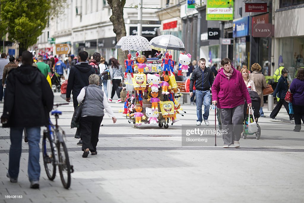 Pedestrians pass a street vendor selling novelty items based on children's television characters in Cardiff, U.K. on Thursday, May 23, 2013. Bank of England Markets Director Paul Fisher said policy makers must continue to provide support to the British economy so that companies and consumers have room to reduce debts and rebuild confidence. Photographer: Simon Dawson/Bloomberg via Getty Images