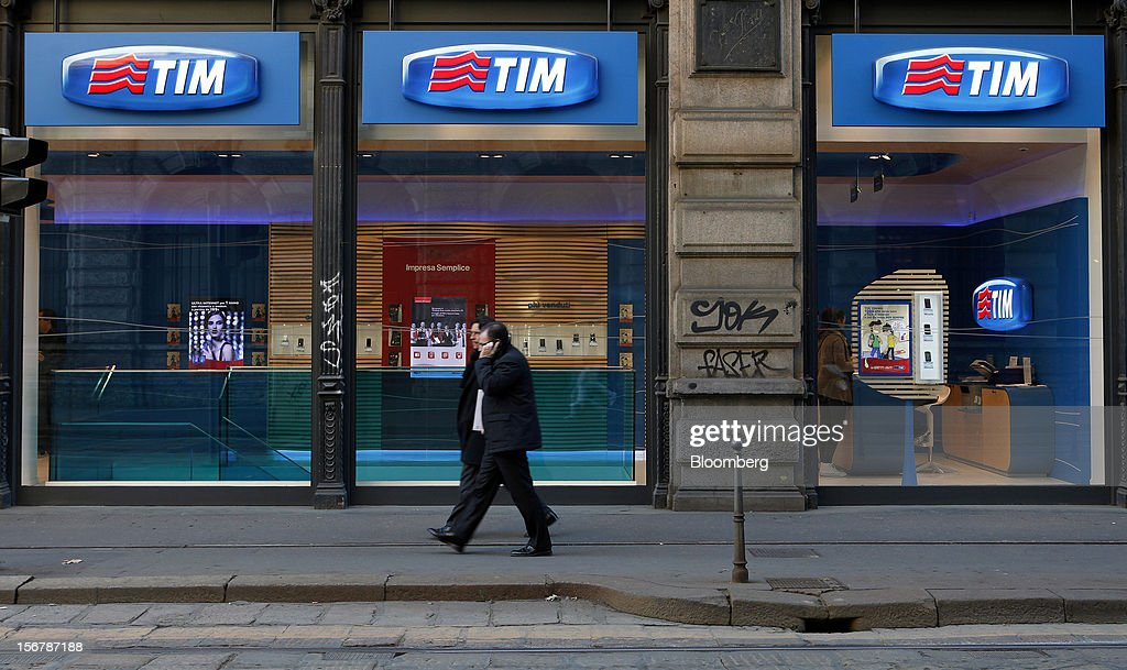 Pedestrians pass a TIM store, the mobile unit of Telecom Italia SpA, in Milan, Italy, on Tuesday, Nov. 20, 2012. Telecom Italia SpA said it is still reviewing the possible spinoff of its fixed-line network and the company's board will discuss the outcome of its analysis on Dec. 6. Photographer: Alessia Pierdomenico/Bloomberg via Getty Images