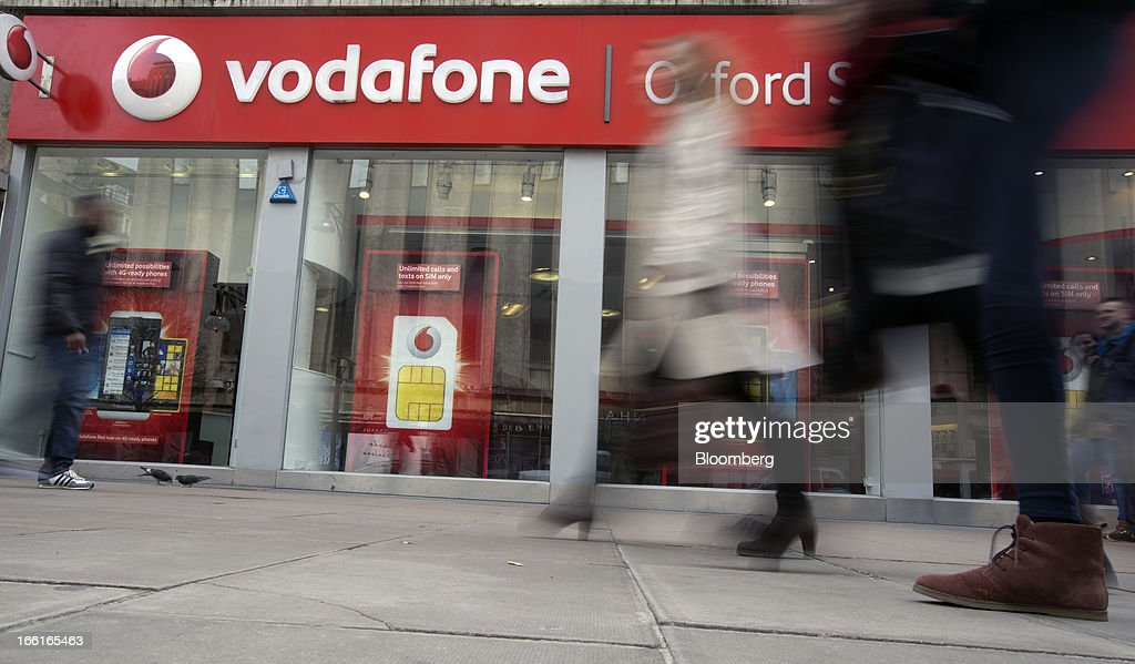 Pedestrians pass a Vodafone Group Plc store on Oxford Street in London, U.K., on Monday, April 8, 2013. Vodafone Group Plc is restating its results going back two fiscal years as new international accounting rules for joint ventures cut historical revenue and earnings. Photographer: Simon Dawson/Bloomberg via Getty Images