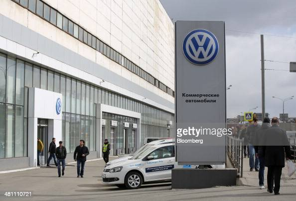 Pedestrians pass a VW logo on display outside a Volkswagen AG automobile dealership in Moscow Russia on Friday March 28 2014 Foreign companies face...