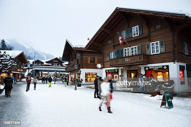 Pedestrians pass a watch store advertising Rolex and Patek Philippe brands on the promenade in Gstaad Switzerland on Saturday Jan 19 2013 Options...