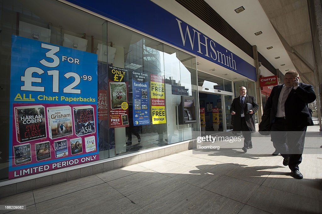 Pedestrians pass a WH Smith Plc store advertising products for sale in London, U.K., on Wednesday, April 10, 2013. WH Smith Plc, the book and magazine retailer with more than 1,100 U.K. outlets, is scheduled to announce earnings on April 11. Photographer: Simon Dawson/Bloomberg via Getty Images