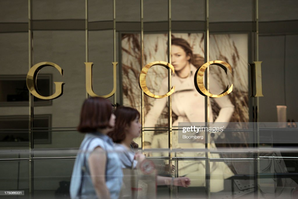 Pedestrians pass a window display at a Gucci store operated by Kering SA at the Shinsegye Co department store at Time Square in Seoul South Korea on...