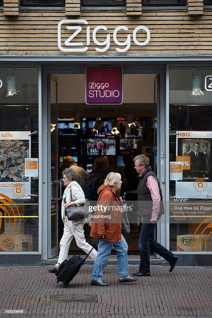 Pedestrians pass a Ziggo NV store in Utrecht, Netherlands, on Friday, Oct. 4, 2013. Cable-TV provider Ziggo, which is 28.5 percent owned by Liberty Global Plc, is pushing into the Dutch mobile market with low-priced packages, following a playbook pioneered by French discount operator Iliad SA. Photographer: Jasper Juinen/Bloomberg via Getty Images