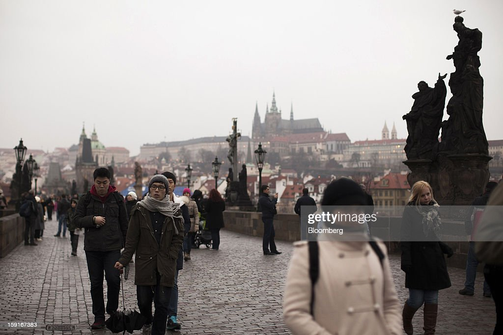 Pedestrians pass across the historic Charles bridge in Prague, Czech Republic, on Tuesday, Jan. 8, 2013. The Czech economy is showing weak domestic demand as households and businesses cut spending due to government austerity programs and the euro area's debt crisis. Photographer: Bartek Sadowski/Bloomberg via Getty Images