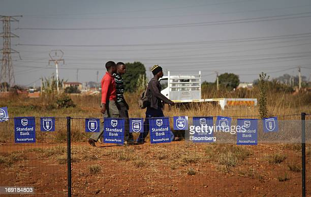 Pedestrians pass advertisements for MPesa mobile phone money transfer services operated by Standard Bank Group Ltd outside a supermarket in Tembisa...