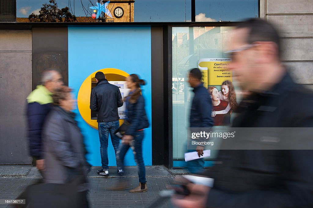 Pedestrians pass along a street while a customer withdraws cash from an automated teller machine (ATM) outside a CaixaBank SA branch in Barcelona, Spain, on Wednesday, March 20, 2013. Officials from the troika of international creditors -- the ECB, the International Monetary Fund and the European Commission -- are in Cyprus discussing further capital controls and possibly extending a bank holiday to the end of the week, a European official familiar with the talks said on condition of anonymity because the discussions are confidential. Photographer: David Ramos/Bloomberg via Getty Images