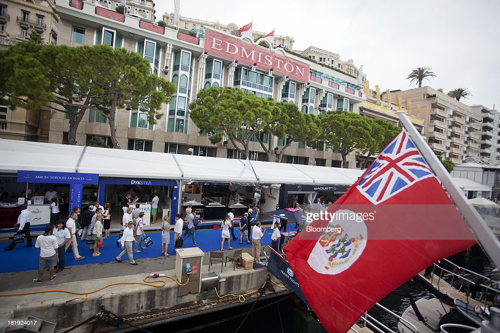 Pedestrians pass along the quayside as trade stands sit during the Monaco Yacht Show (MYS) in Monaco, France, on Thursday, Sept. 26, 2013. Over 100 of the world's luxury yachts will be displayed in Port Hercules during the 23rd MYS which runs from Sept. 25 - 28. Photographer: Balint Porneczi/Bloomberg via Getty Images