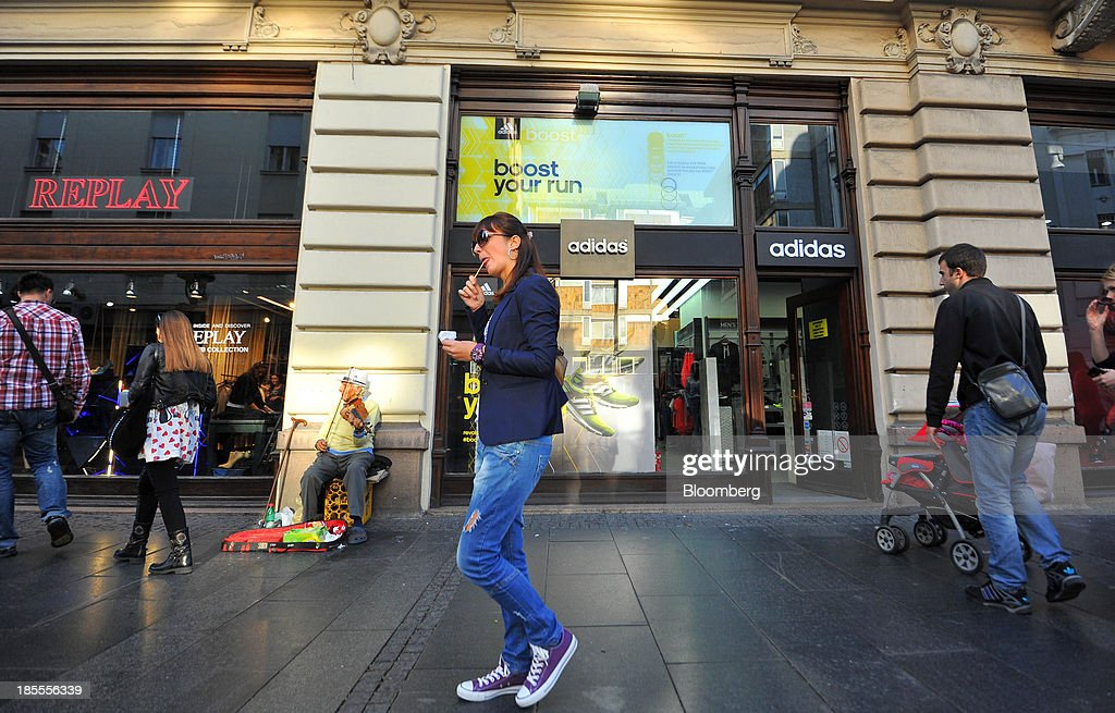 Pedestrians pass an adidas AG store in Belgrade, Serbia, on Sunday, Oct. 20, 2013. Serbia's government revealed a salvo of measures to bring the public finance deficit and debt back under control by 2017 after the head of the largest coalition party warned the country was on the brink of insolvency. Photographer: Oliver Bunic/Bloomberg via Getty Images