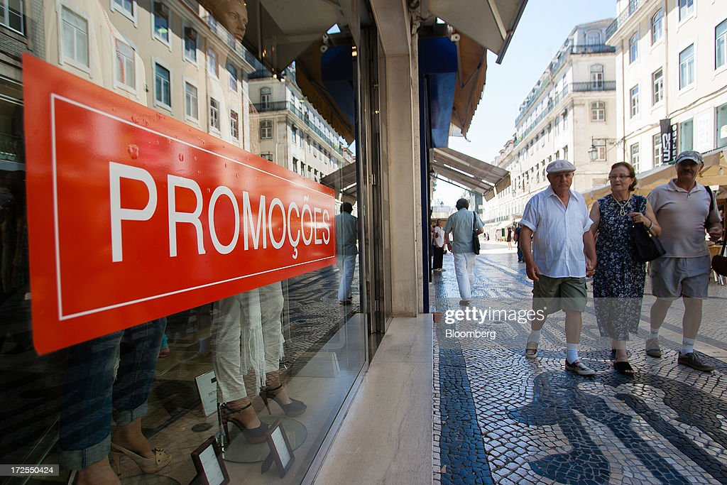 Pedestrians pass an advertisement for a sales promotion in the window of a retail store in Lisbon, Portugal, on Wednesday, July 3, 2013. Portuguese borrowing costs topped 8 percent for the first time this year after two ministers quit, signaling the government will struggle to implement further budget cuts as its bailout program enters its final 12 months. Photographer: Mario Proenca/Bloomberg via Getty Images