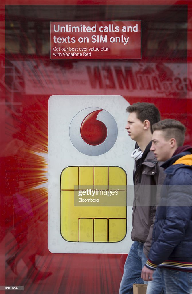 Pedestrians pass an advertisement for mobile phone SIM card offers in the window display of a Vodafone Group Plc store on Oxford Street in London, U.K., on Monday, April 8, 2013. Vodafone Group Plc is restating its results going back two fiscal years as new international accounting rules for joint ventures cut historical revenue and earnings. Photographer: Simon Dawson/Bloomberg via Getty Images