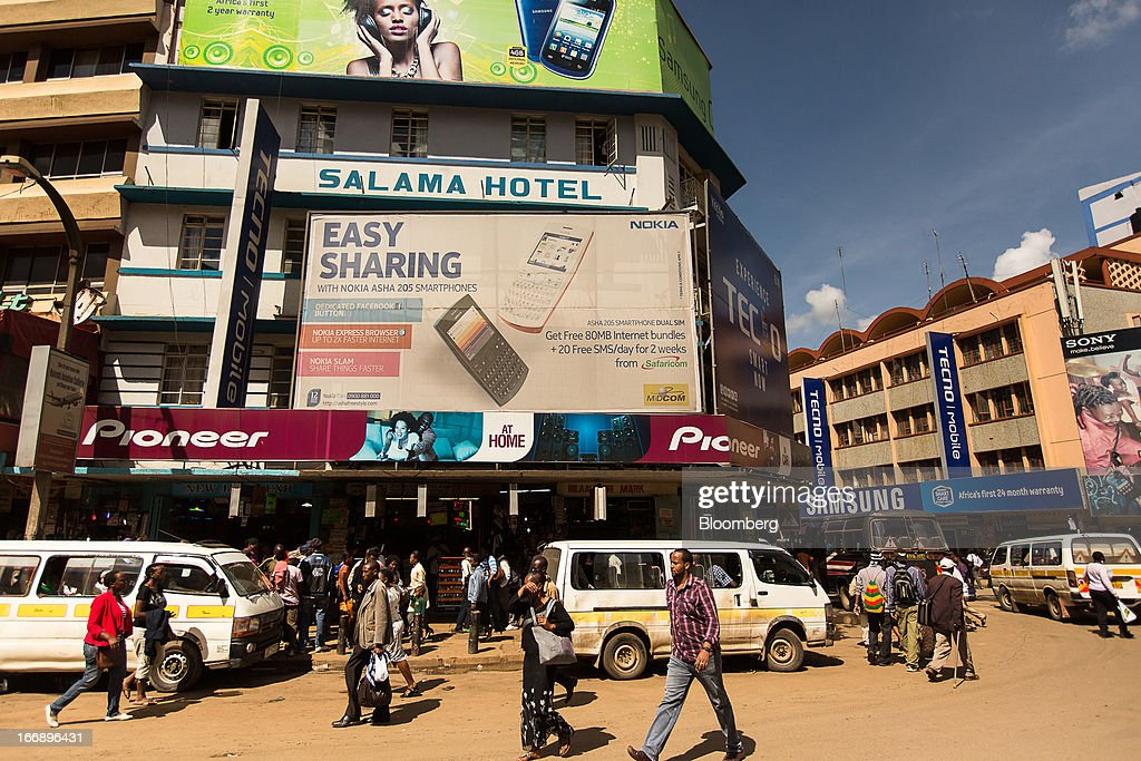 Pedestrians pass an advertisement for the Nokia Asha 205 smartphone in Nairobi, Kenya, on Wednesday, April 17, 2013. Though only 23 percent of houses there have electricity and just 9 percent of roads are paved, mobile-phone penetration is 75 percent in the country, up from 5 percent in 2003. Photographer: Trevor Snapp/Bloomberg via Getty Images