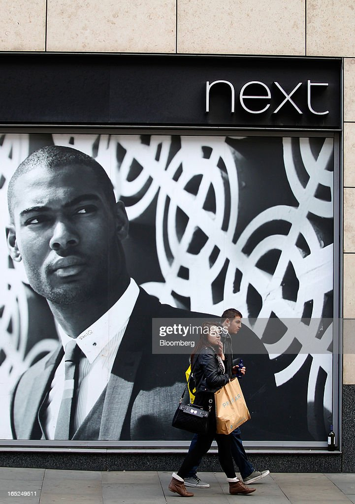 Pedestrians pass an advertisement in the window of a Next Plc store in Manchester, U.K., on Monday, April 1, 2013. U.K. retail sales unexpectedly stagnated in March in a sign that consumer spending remains under pressure from higher energy bills and weak wage growth. Photographer: Paul Thomas/Bloomberg via Getty Images