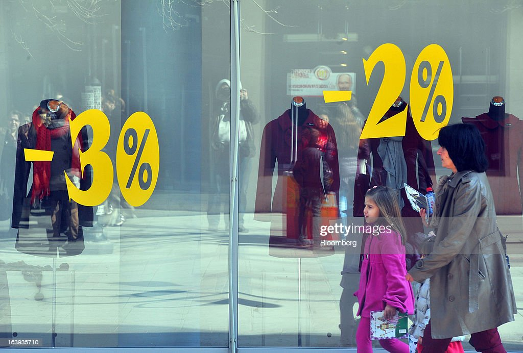 Pedestrians pass an advertisement offering sale discounts in the window of a fashion store in central Skopje, Macedonia, on Sunday, March 17, 2013. Macedonia's economy contracted by a real 0.3% on the year in 2012, compared to a growth of 2.8% a year earlier, an estimate released by the country's statistics office showed. Photographer: Oliver Bunic/Bloomberg via Getty Images