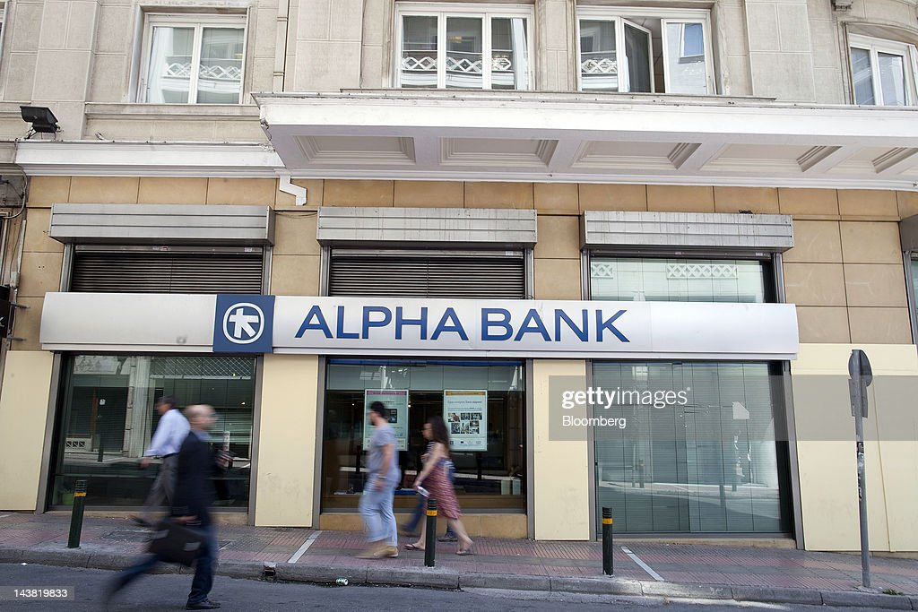 Pedestrians pass an Alpha Bank AE branch in Athens, Greece, on Friday, May 4, 2012. European stocks dropped as investors awaited today's American payrolls report and elections in France, Greece, Italy and Germany this weekend. Photographer: Simon Dawson/Bloomberg via Getty Images