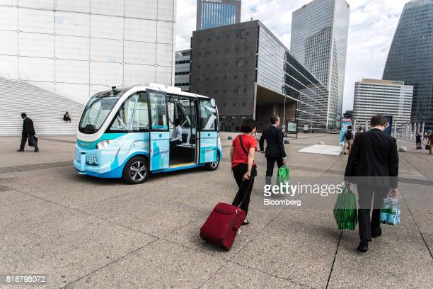 Pedestrians pass an Arma autonomous shuttle bus manufactured by Navya Technologies SAS in La Defense business district of Paris France on Wednesday...