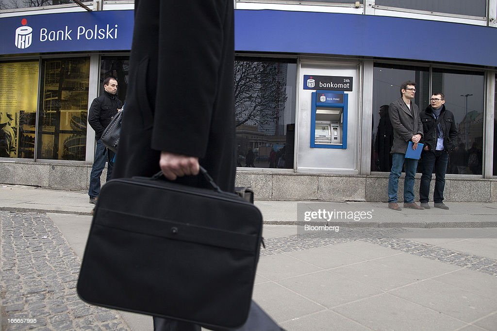 Pedestrians pass an automated teller machine (ATM) outside a PKO Bank Polski SA bank branch in Warsaw, Poland, on Thursday, April 11, 2013. Poland's central bank kept interest rates unchanged at a record-low 3.25 percent yesterday. Photographer: Bartek Sadowski/Bloomerg