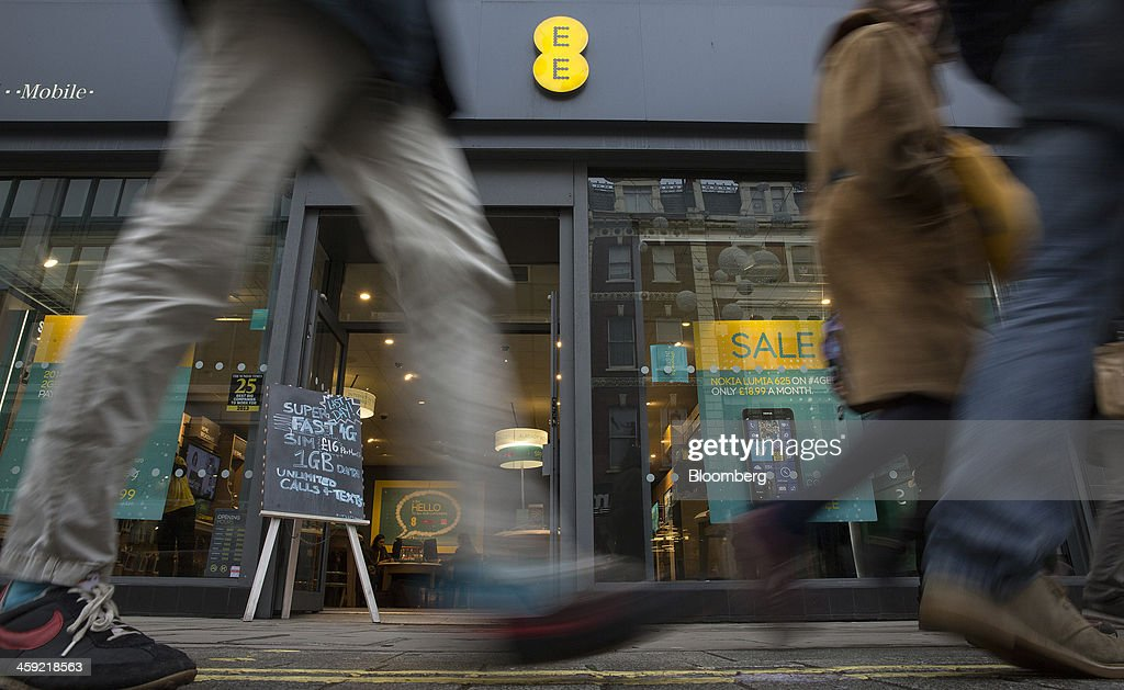 Pedestrians pass an EE mobile phone store in London, U.K., on Tuesday, Dec. 24, 2013. Vodafone Group Plc; EE, which is co-owned by Orange SA and Deutsche Telekom AG; Three, owned by Hutchison Whampoa Ltd.; and Virgin Media Inc. said they will cap bills run up on phones reported lost or stolen, stop mid-contract price increases, and support the U.K. government in its attempt to end roaming charges within the European Union. Photographer: Simon Dawson/Bloomberg via Getty Images
