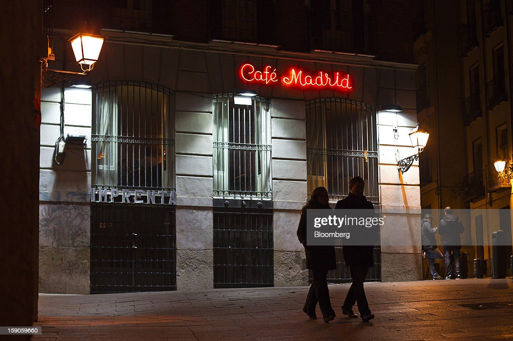 Pedestrians pass an electric sign illuminated at night outside Cafe Madrid in Madrid, Spain, on Sunday, Jan. 6, 2013. In December, the Spanish parliament passed an energy law that imposed a 7 percent tax on electricity generation from Jan. 1 to plug the deficit. Photographer: Angel Navarrete/Bloomberg via Getty Images