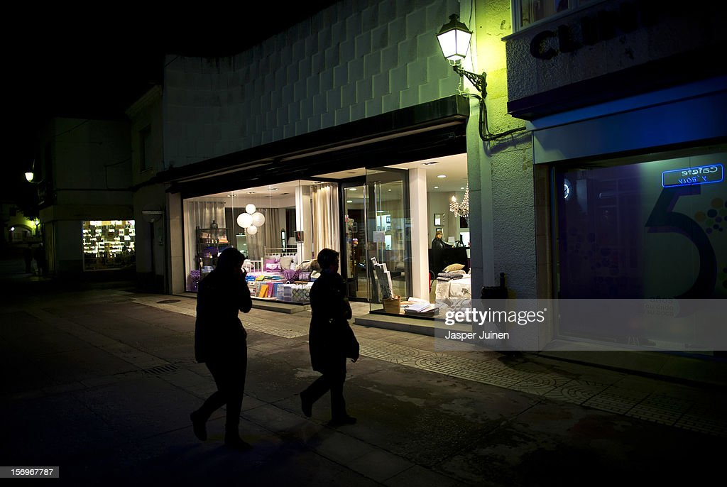 Pedestrians pass an empty shop in Calle Mayor on a Friday night, a typical night for Spaniards to shop and hang out, as a sales woman inside waits for clients on November 23, 2012 in Villacanas, Spain. During the boom years, where in its peak Spain built some 800,000 houses a year accompanied by the manufacturing of millions of wooden doors where needed, the people of Villacanas were part of Spain's middle class enjoying high wages and permanent jobs. During the construction boom years the majority of the doors used within these new developments were made in this small industrial town. Approximately seven million doors a year were once assembled here and the factory employed a workforce of almost 5700 people, but the town is now left almost desolate with the Villacanas industrial park now empty and redundant. With Spain in the grip of recession and the housing bubble burst, Villacanas is typical of many former buoyant industrial Spanish towns now struggling with huge unemployment problems.