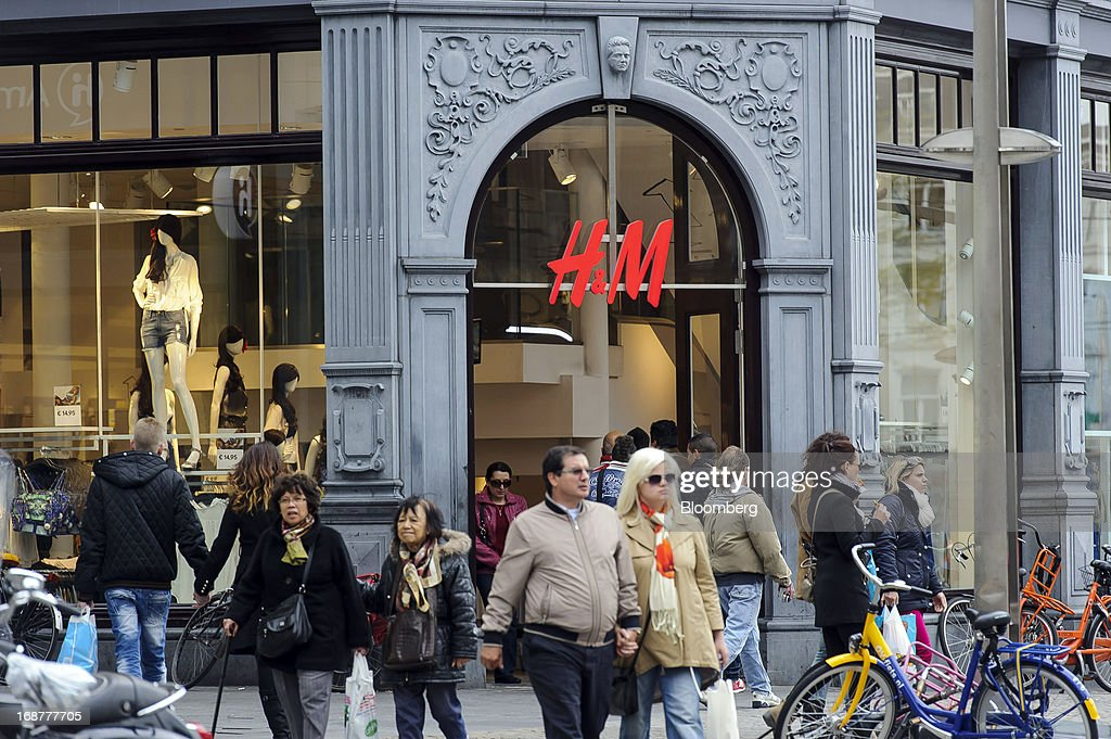 Pedestrians pass an H&M fashion store, operated by Hennes & Mauritz AB (H&M) in the Dutch city of Amsterdam, Netherlands, on Tuesday, May 14, 2013. Euro-area data this week will probably reveal economic scars of the sovereign debt crisis confirming that the region is now suffering the longest recession since the single currency's creation. Photographer: Jock Fistick/Bloomberg via Getty Images