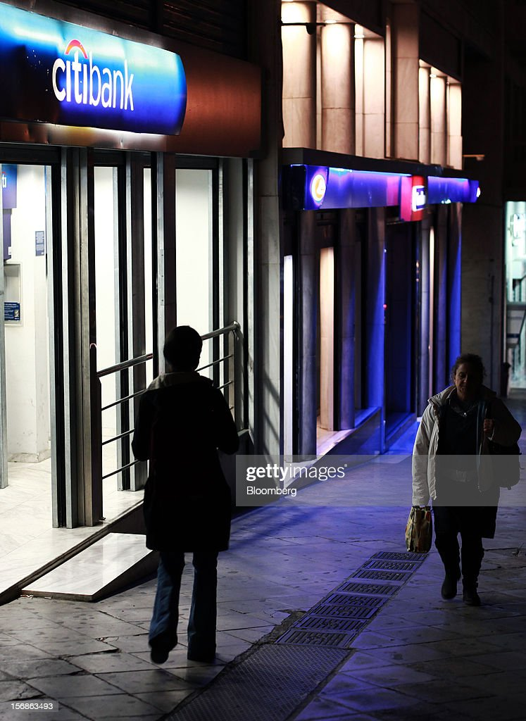 Pedestrians pass an illuminated Citibank branch, operated by Citigroup Inc., in central Athens, Greece, on Thursday, Nov. 22, 2012. Citigroup Inc., the third-biggest U.S. bank by assets, said it will shutter almost half of its branches in Greece as European lawmakers continue a three-year struggle to fix the country's economy. Photographer: Angelos Tzortzinis/Bloomberg via Getty Images