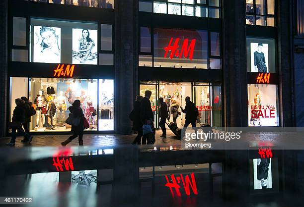 Pedestrians pass an illuminated Hennes Mauritz AB clothing fashion store in Berlin Germany on Wednesday Jan 7 2015 As European Central Bank policy...