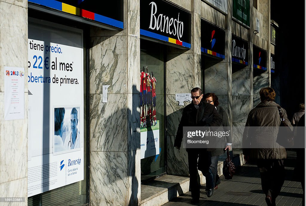 Pedestrians pass Banesto signs above a Banco Espanol de Credito SA bank branch in Barcelona, Spain, on Tuesday, Jan. 8, 2013. Banco Santander SA, Spain's biggest lender, will offer 263 million euros ($345 million) in stock to buy out minority investors in its Banco Espanol de Credito SA retail unit and close 700 local branches to cut costs. Photographer: David Ramos/Bloomberg via Getty Images