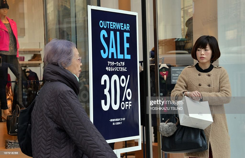 Pedestrians pass before a discount sale sign at an aparel shop in Tokyo on November 14, 2013. Japan said that growth halved in the September quarter as exports slipped and consumer spending slowed, in a worrying sign for Tokyo's bid to kickstart the world's third-largest economy. Official data showed the economy expanded by 0.5 percent in the three months to September, slightly higher than economists' expectations but a marked slowdown from 0.9 percent growth in the previous quarter. AFP PHOTO / Yoshikazu TSUNO